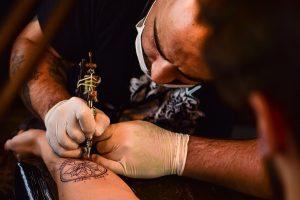 Tätowierer sticht Tattoos auf Unterarm